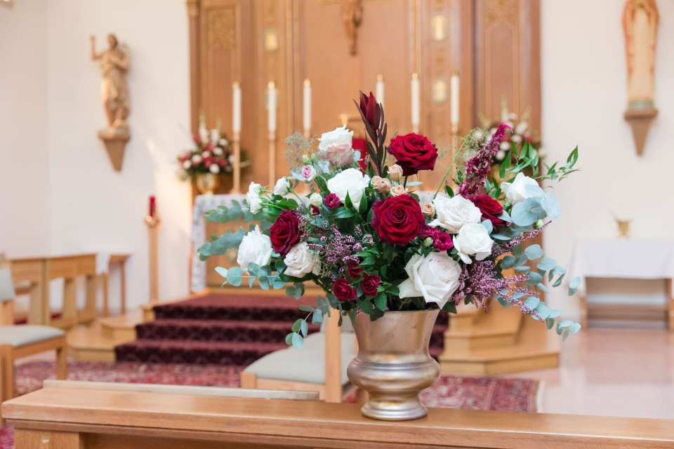 ceremony altar floral arrangement of roses in reds and whites, along witha . mix of greens and other wild flowers in the same shades in a silver urn by Ivy on Main