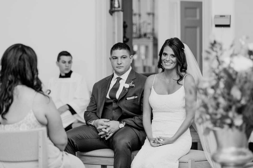 black and white photo of the bride and groom sitting down during the formal catholic wedding ceremony