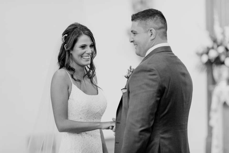 black and white candid photo of the bride and groom during their vows