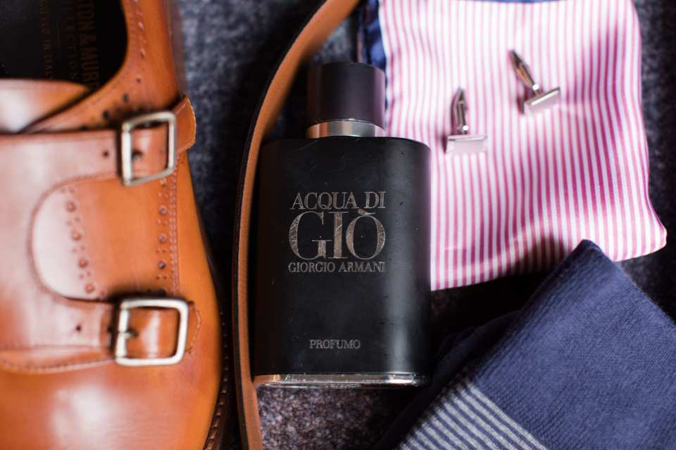 the grooms accessories of shoes, belt, cologne, kerchief, cuff links