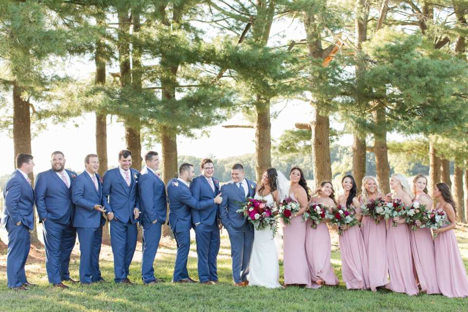 Informal and fun wedding party photo amongst the trees at the Laurita Winery. Men in blue suits by Generation Tux, women in pink gowns by Azazie, florals by Ivy on Main
