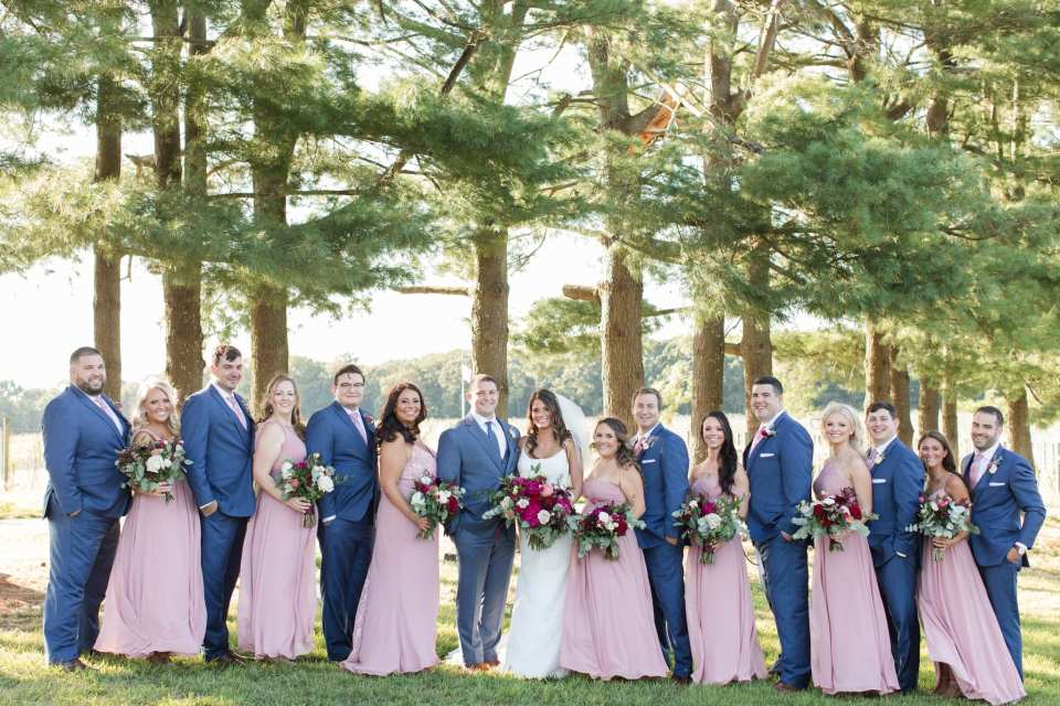 formal wedding party photo amongst the trees at the Laurita Winery. Men in blue suits by Generation Tux, women in pink gowns by Azazie, florals by Ivy on Main