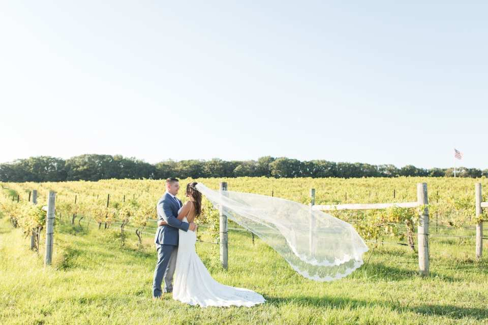 The bride in a gown by Mikella, groom in a tuxedo suit by Generation Tux, embrace at the waist, amongst the vines at the vineyard at Laurita Winery in New Jersey the brides veil flowing in the air behind her, by Jaye Kogut Photography