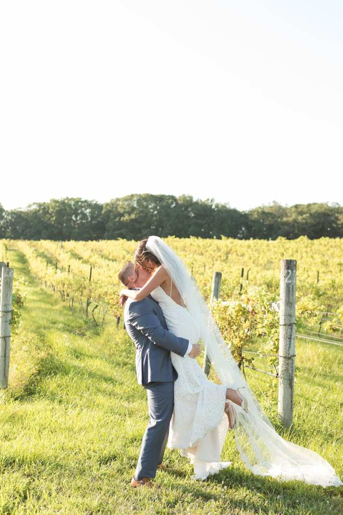 The bride in a gown by Mikella being lifted up in the air while kissing her groom, amongst the vines at the vineyard at Laurita Winery in New Jersey by Jaye Kogut Photography