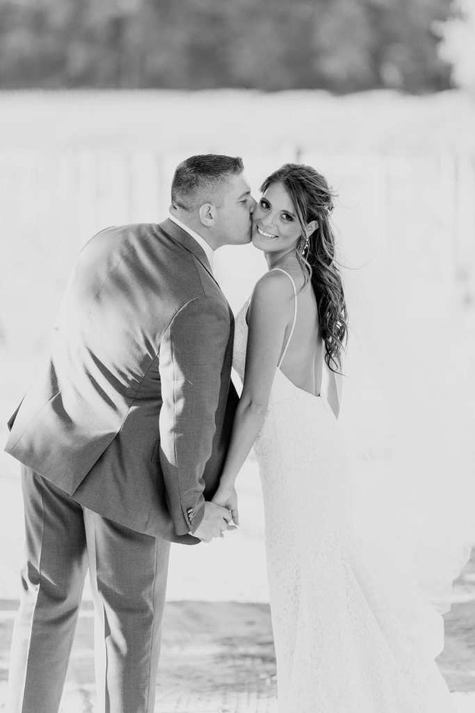Black and white photo of the bride and groom holding hands, the groom kissing the brides cheek as she looks back at the camera