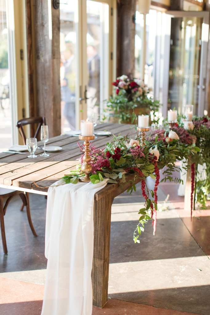 the wooden sweetheart table with low floral arrangement by Ivy on Main consisting of greenery, burgundy florals and white candles on top of gold pillars.