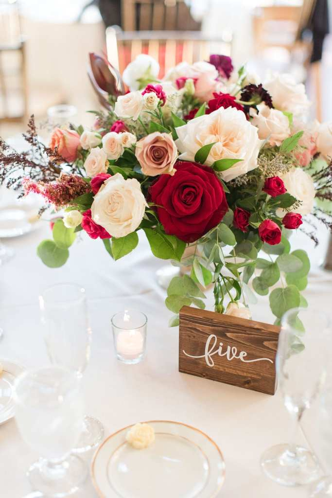 low table arrangement of greenery, white, pink, cream, red and burgundy florals by Ivy on Main with a wooden table number indicating table five