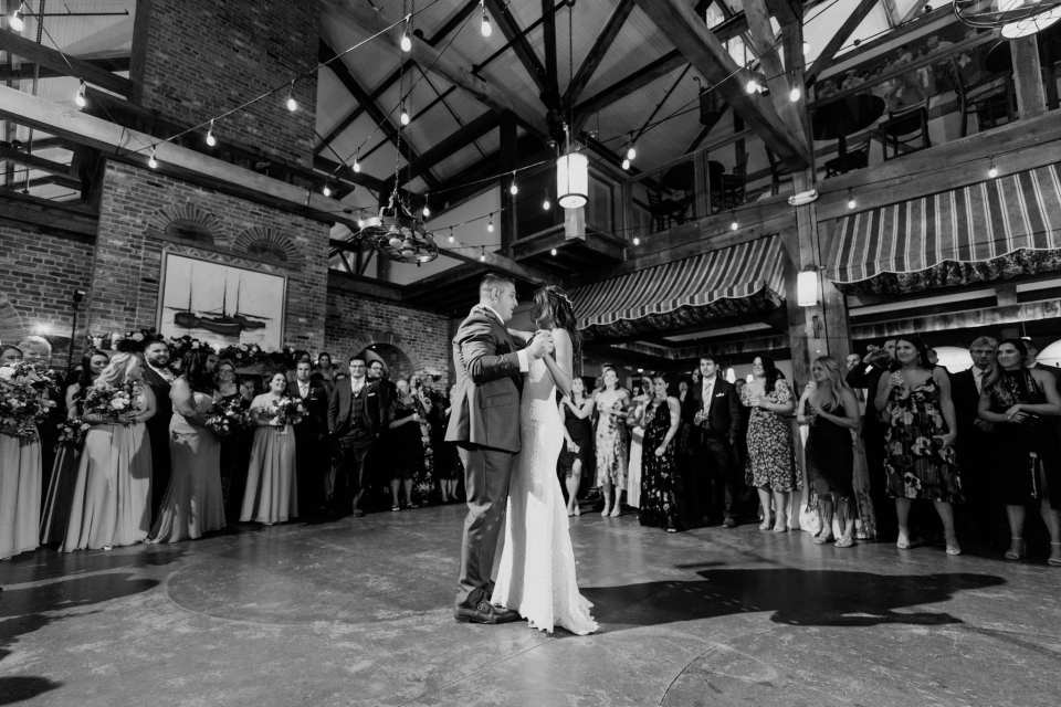 Black and white wide shot of the bride and groom dancing their first dance as guests and wedding party look on at the Laurita Winery