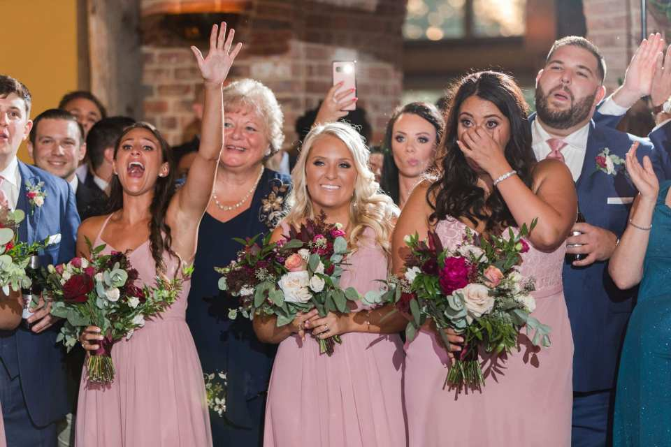 Members of the bridal party, in pink gowns by Azazie hold their bouquets of greens with dark pink, burgundy and white florals while watching the bride and groom share a dance