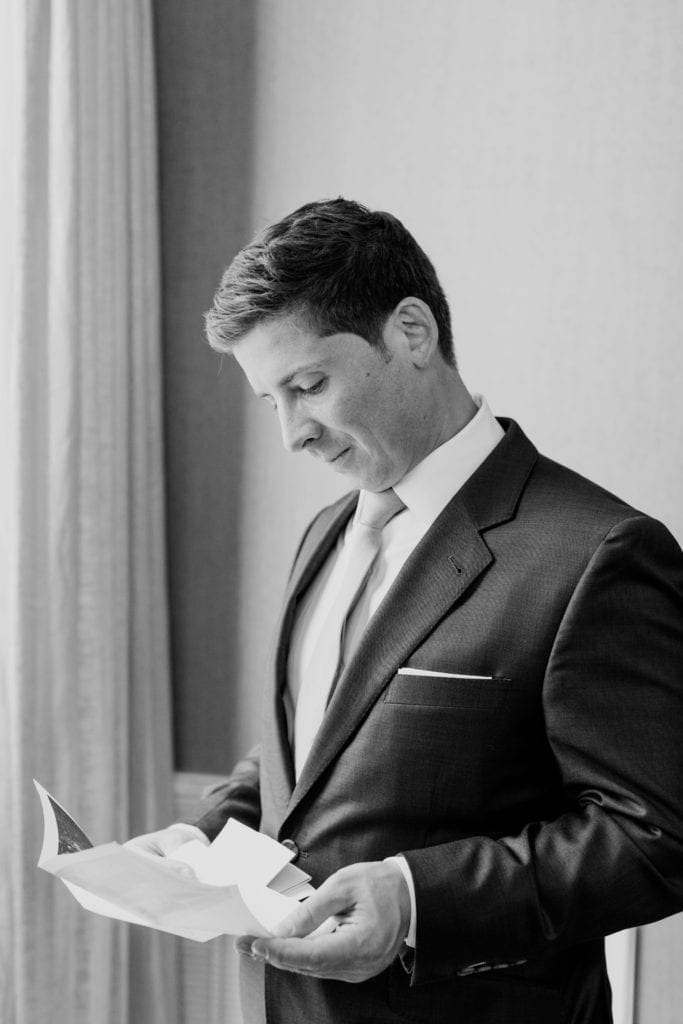Black and white photo of the groom reading a letter from his bride