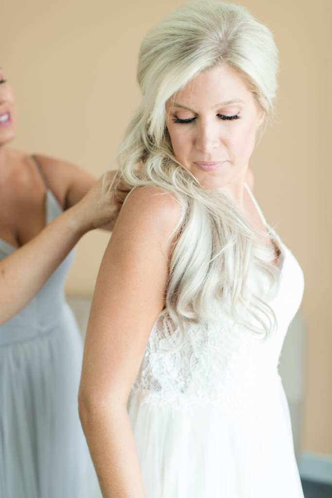 The bride being helped into her gown by a member of the bridal party in a light blue gown