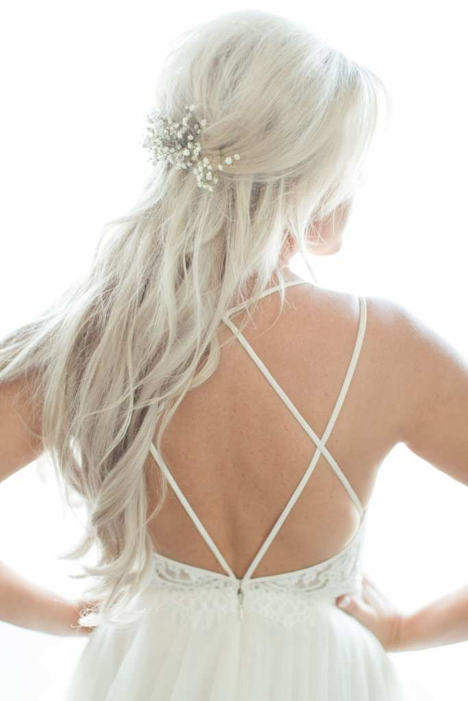 Portrait of the bride from behind, showcasing the crisscross straps on the back of her gown and the baby's breath in her hair