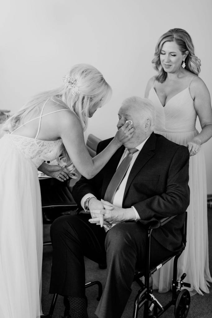 Black and white photo of the bride wiping tears away from her fathers eyes as her sister looks on