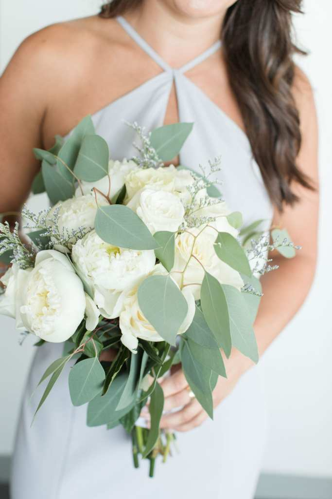 Portrait of a member of the bridal party holding their bouquet of white florals and greens