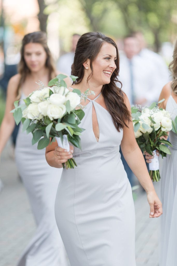 Candid of a member of the bridal party in her light blue gown, walking with the bride and the other members of the bridal party while holding her bouquet of white florals with a small amount of greens
