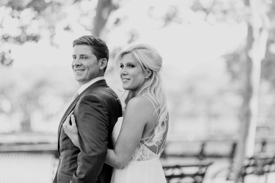 Black and white photo of the bride standing behind the groom, both looking off into the distance