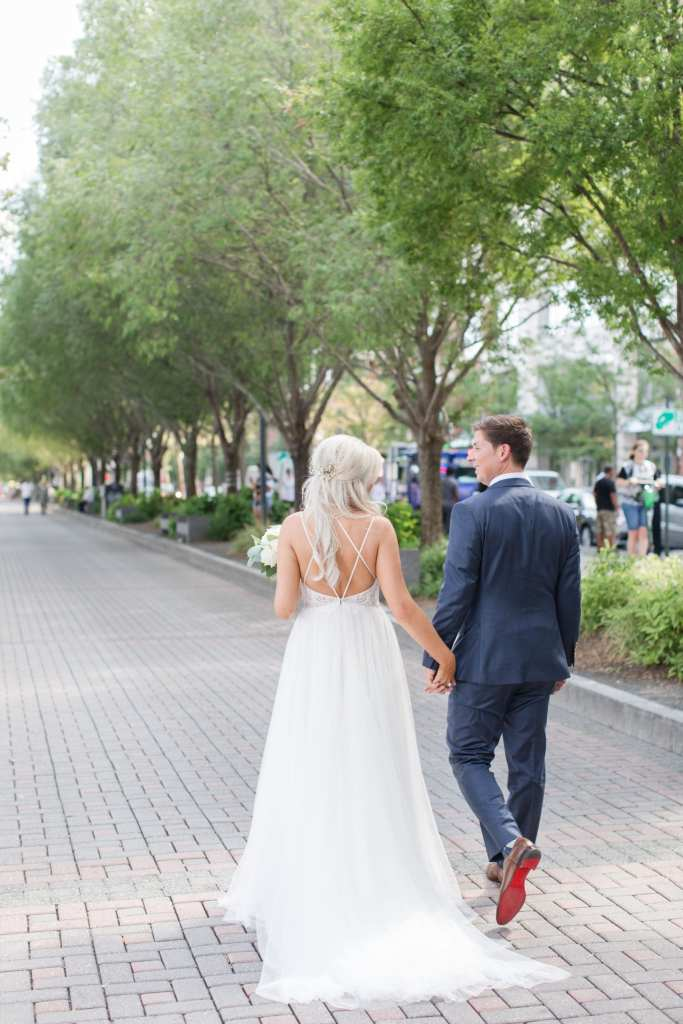 Photo of the bride and groom walking hand in hand from behind on the Hoboken waterfront