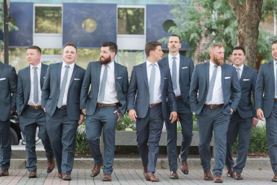 The groom and groomsmen walking outdoors on the Hoboken waterfront