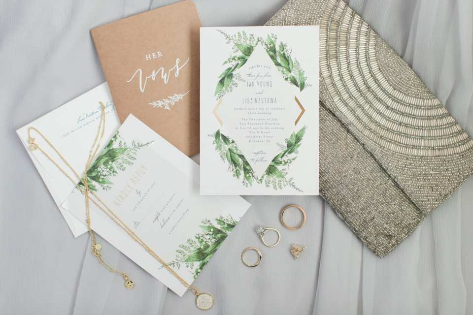 Wedding details: the white and gold with floral accent stationery displayed with the brides vow book, her beaded clutch purse and jewelry