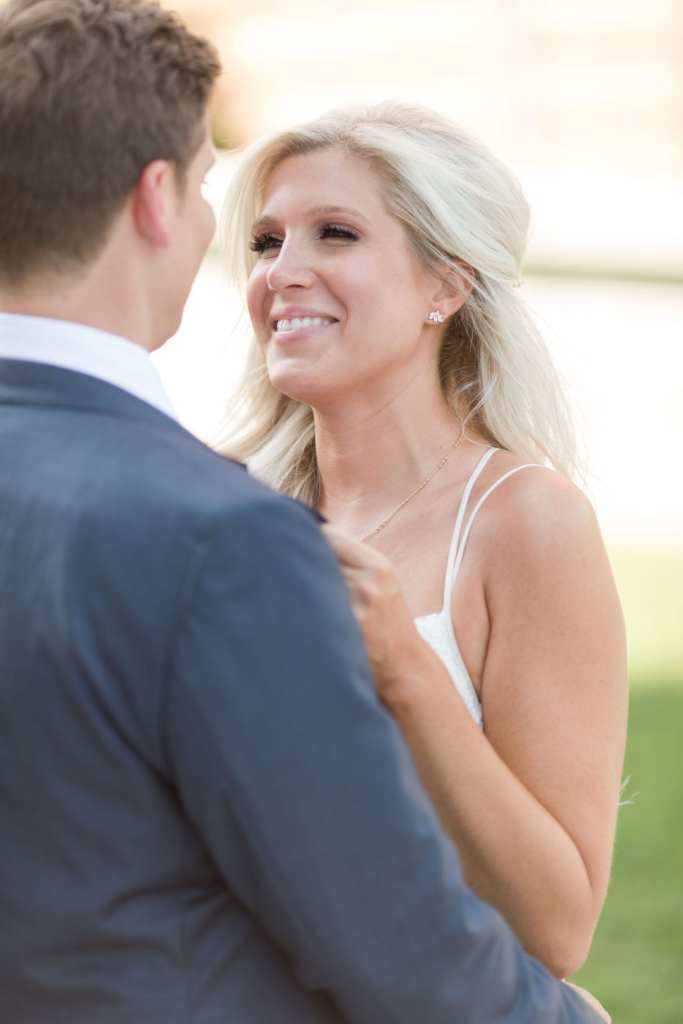 Zoom in on brides face as she is smiling at her groom while in his arms