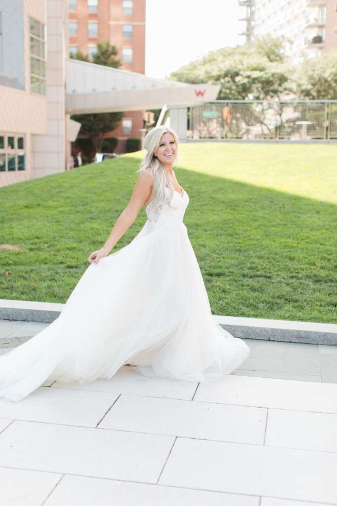 Bride looks at camera while twirling and holding gown