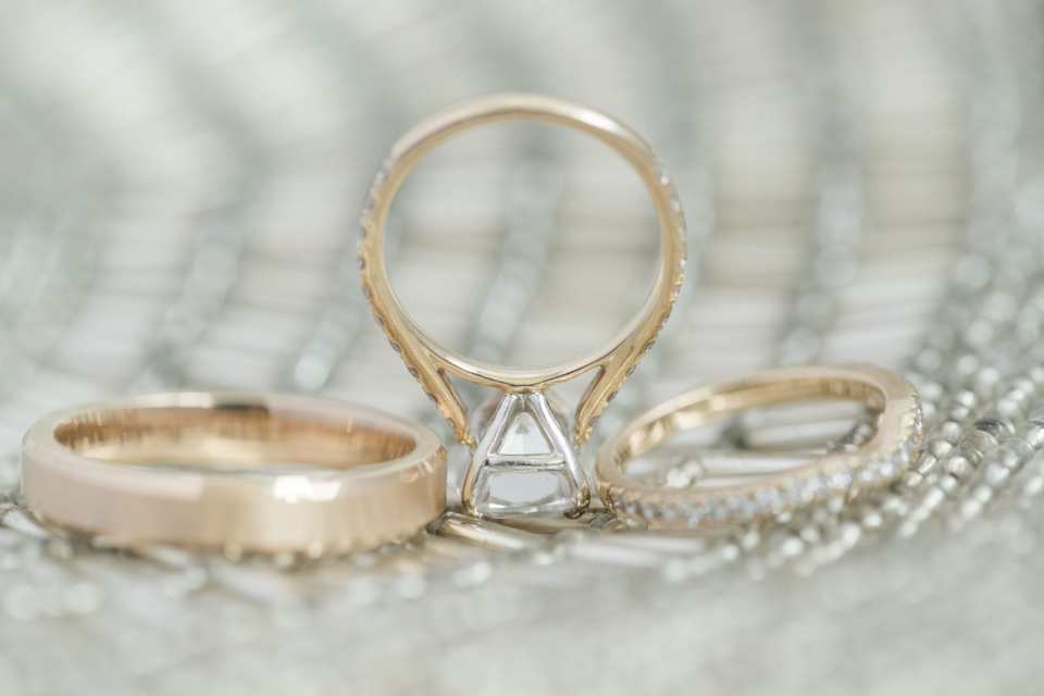 close up of the gold wedding rings and engagement ring