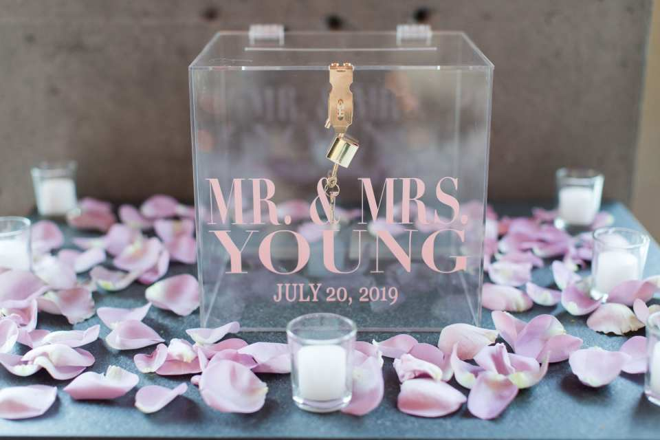 Clear lucite card box with the name of couple and the date of their wedding on it in pink, surrounded by light pink and purple rose petals and votive candles