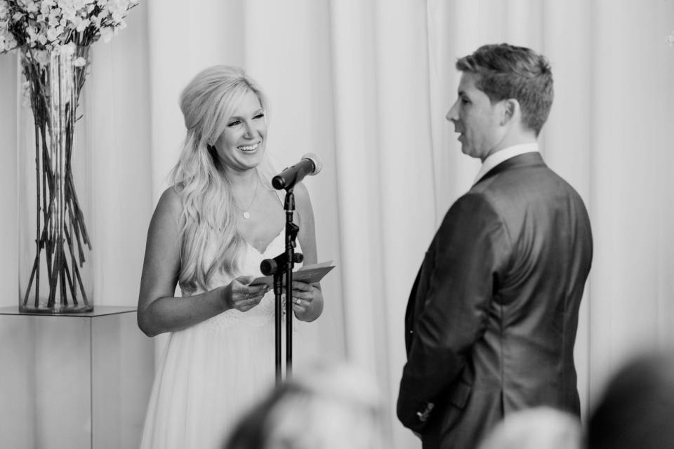 Black and white photo of the bride reading her vows to her groom