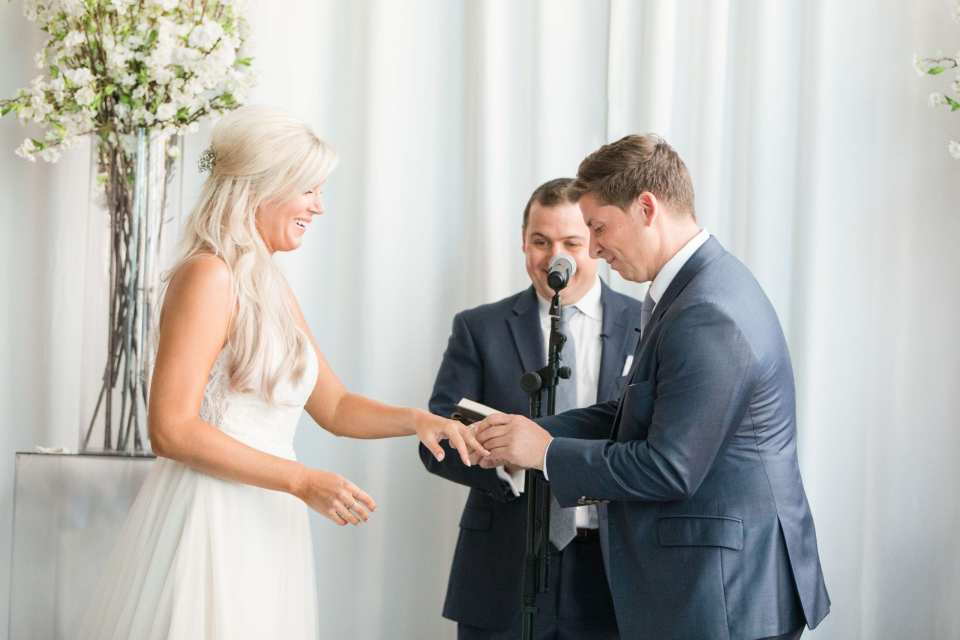 The groom places the wedding band on the left hand of his bride.