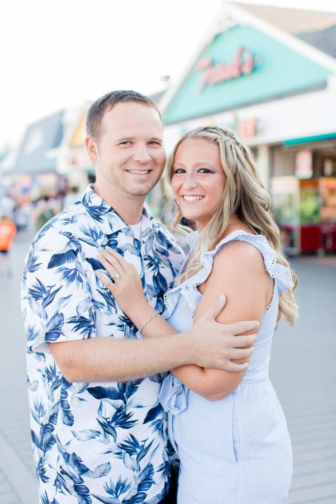 Engaged couple stand facing one another, her left hand on his chest, his right hand under her elbow, Jenkinson's Pavilion behind them by New Jersey wedding photographer Jaye Kogut Photography