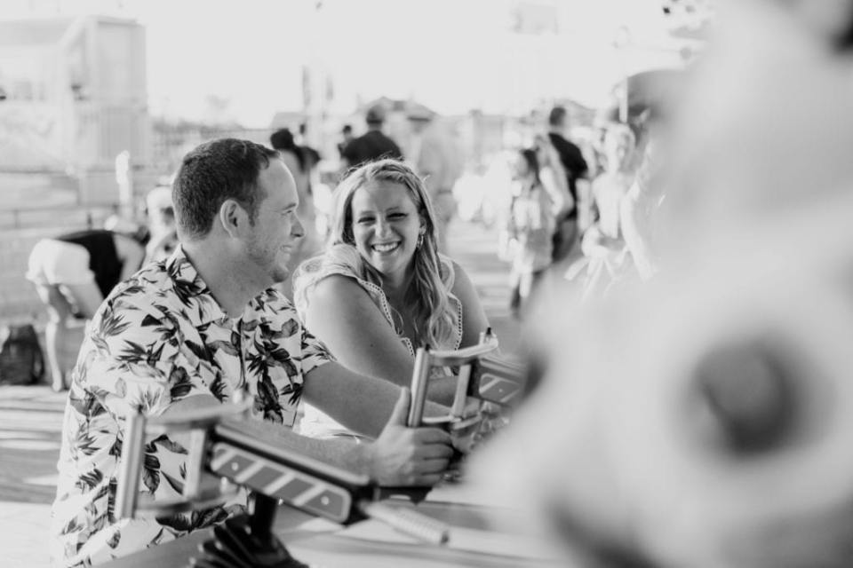 Black and white shot of couple laughing at each other while playing a game at Jenkinson's Pavilion