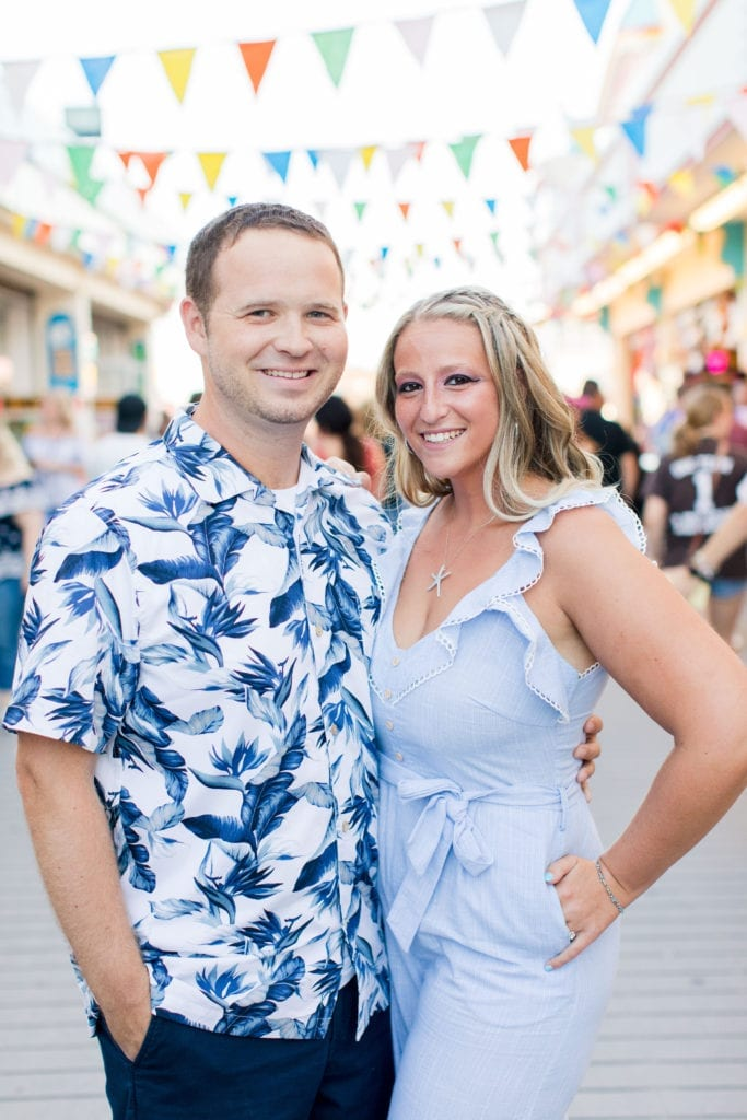 couple standing next to each other, arms around each other, other arm in their hip pocket, on the Jenkinson's Boardwalk