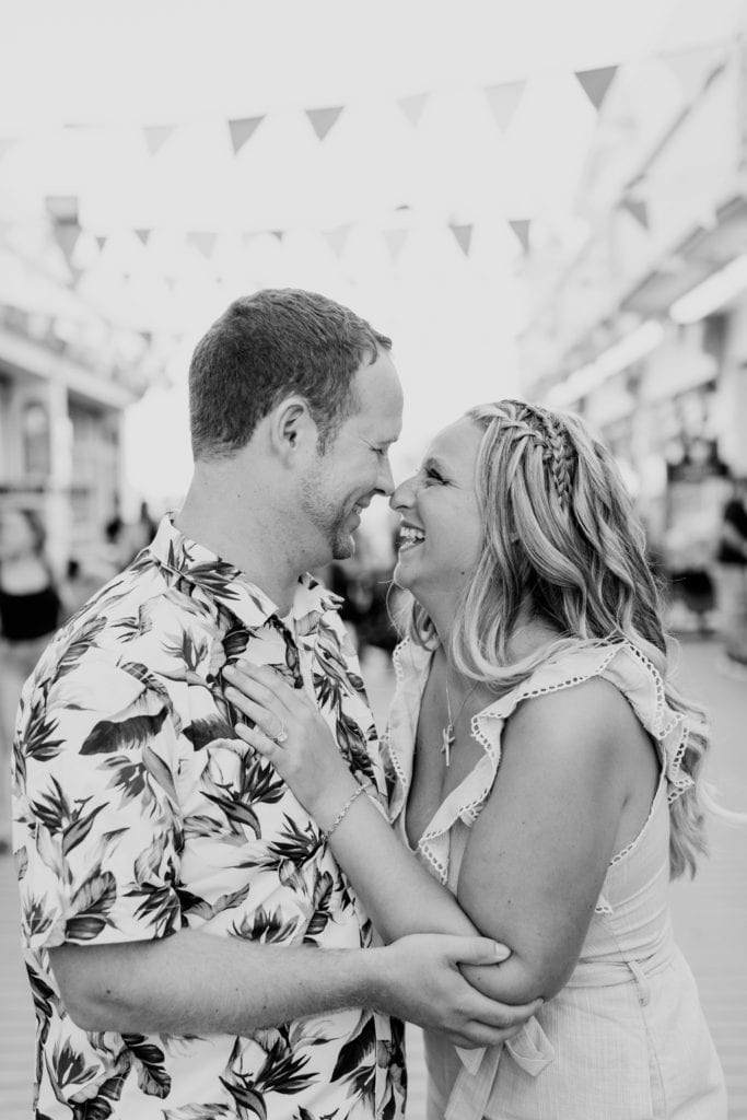 Black and white photo of the bride and groom to be laughing nose to nose, in each others arms on the boardwalk at Jenkinson's Pavilion
