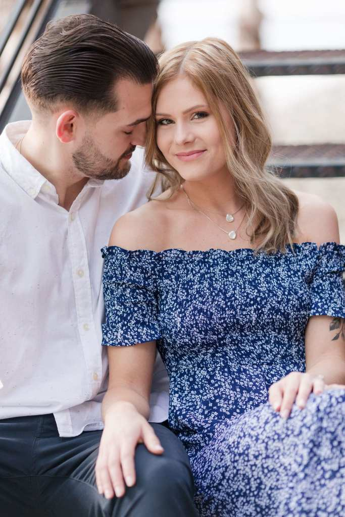 Groom to be in white button down shirt nuzzling his bride to be's hair while she, dressed in an off the shoulder blue print dress, looks towards the camera at the Philadelphia Navy Yard