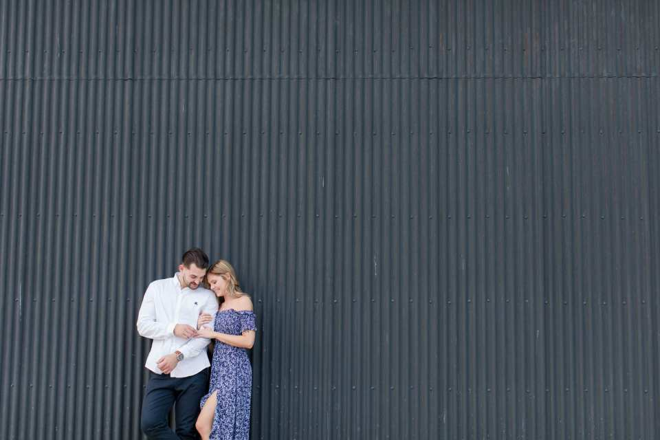 bride and groom to be leaning against grey textured wall in Philadelphia, PA at the Philadelphia Navy Yard