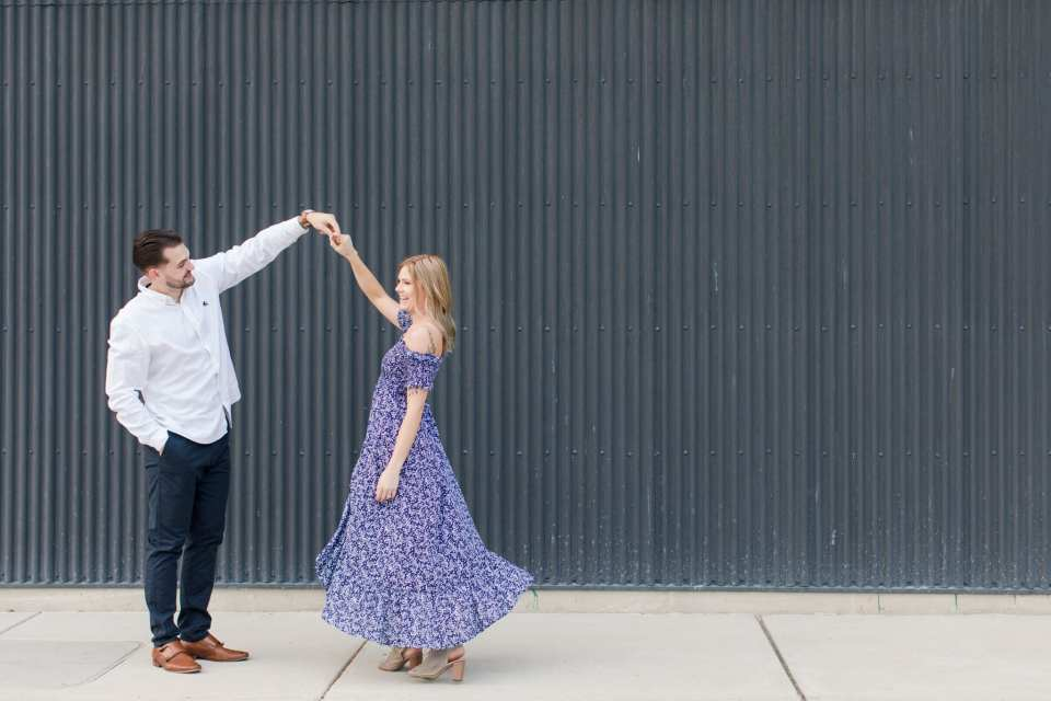 Groom to be twirling his bride to be in front of dark gray textured wall in Philadelphia, PA at the Philadelphia Navy Yard