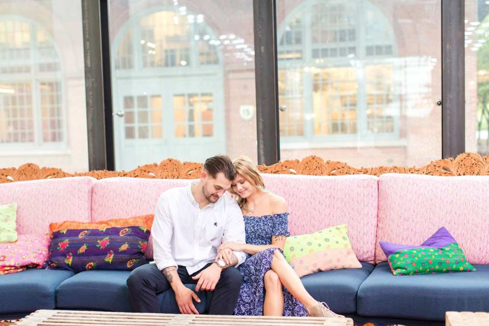 Engaged couple sitting on colorful couch with pink back cushions and blue seat cushions, arm in arm, looking down and admiring her engagement ring