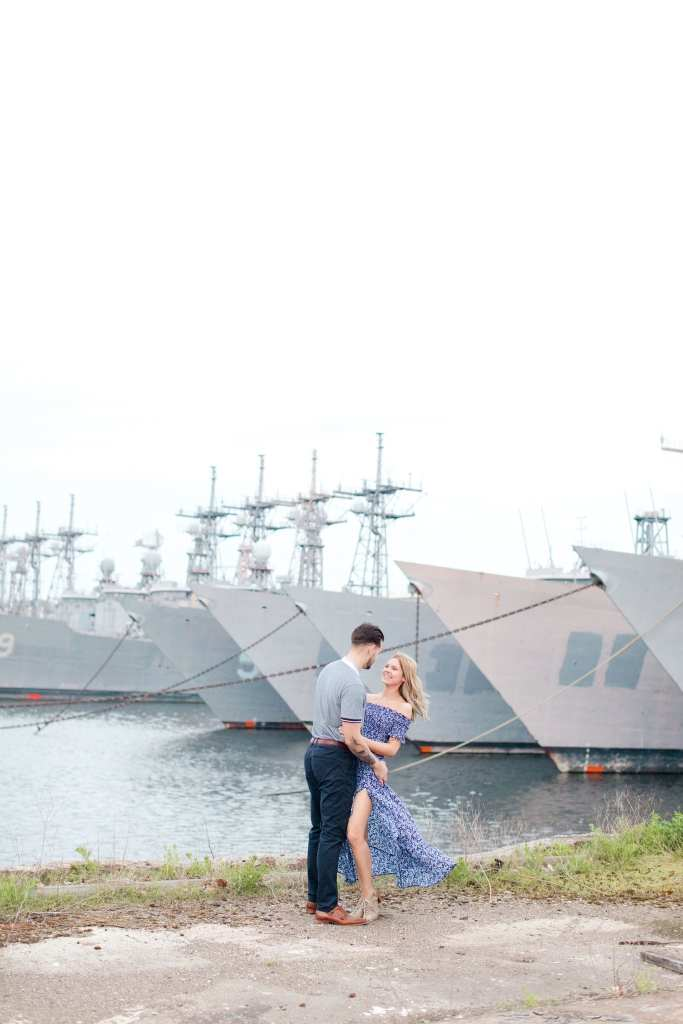 Engaged couple standing facing each other, arms intertwined at the Philadelphia Navy Yard