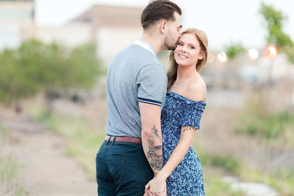 Bride and groom to be standing, bodies facing each other, he is kissing her temple while she is looking past the camera. Outdoors at the Philadelphia Navy Yard
