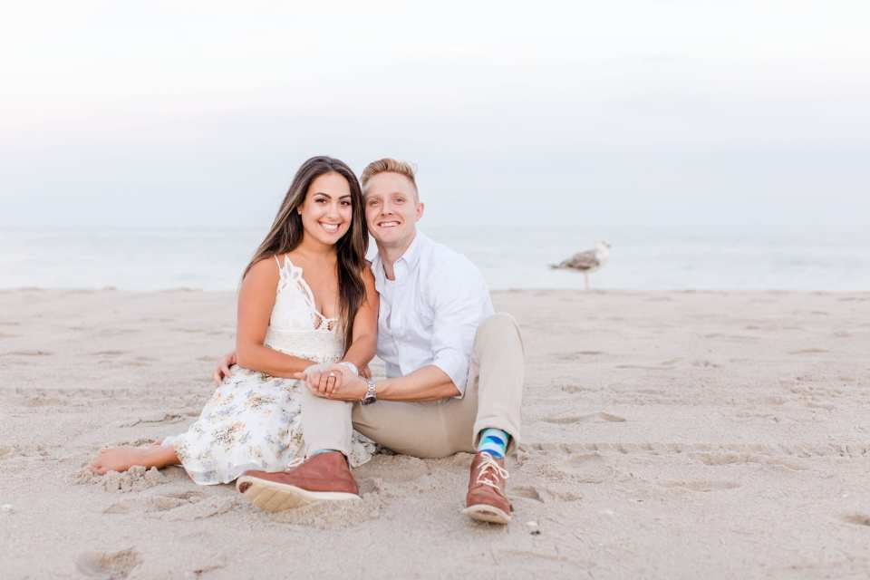Bride to be sitting next to her groom to be on the sand in Point Pleasant