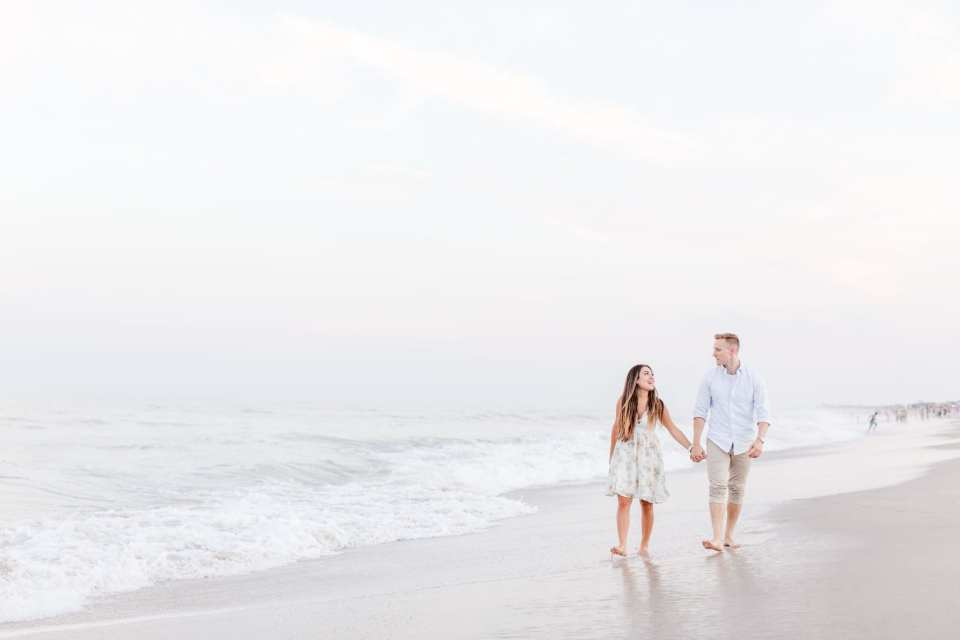 Couple walks hand in hand on the beach, looking at each other, waves rolling in in the background