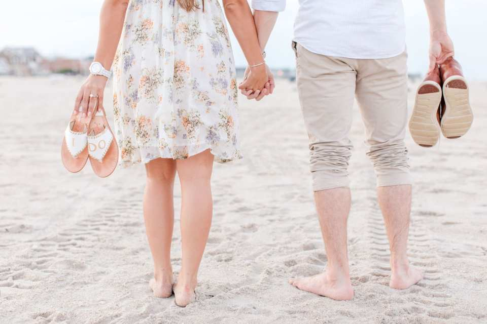 """lower half of body photo walking on beach, hand in hand, with the brides sandals saying """"i do"""""""