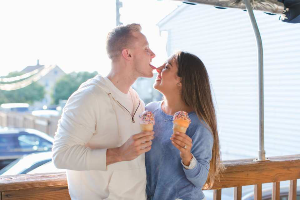 Silly photo of groom to be licking the nose of his bride to be while both having ice cream cones. He is in a white hoodie from J. Crew, she is in blue sweater from Ruby and Jenna