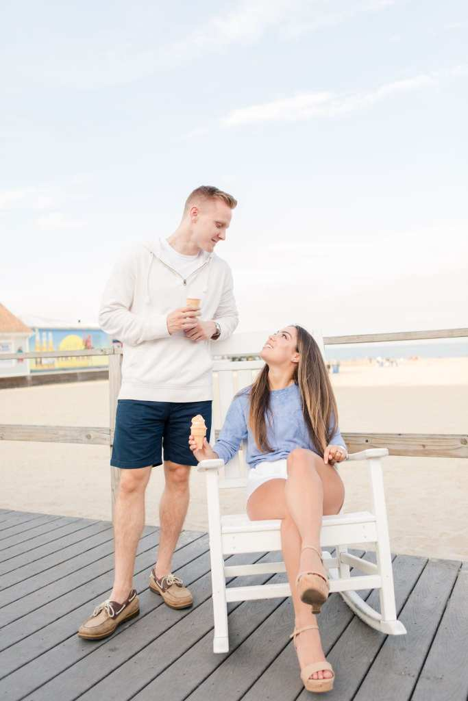 Groom to be in a white hoodie from J. Crew standing behind his bride to be, whom is sitting in a white rocking chair on the boardwalk, both with ice cream cones in their hand on the boardwalk at Jenkinson's Pavilion