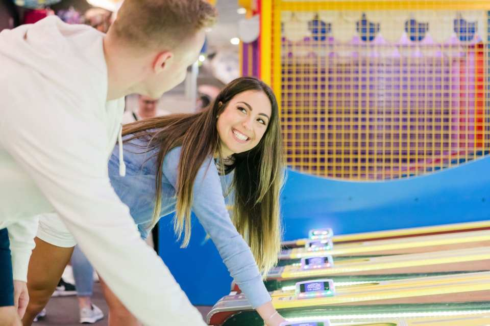 Bride to be smiling at her groom to be as they play skeeball together on Jenkinsons Pavilion