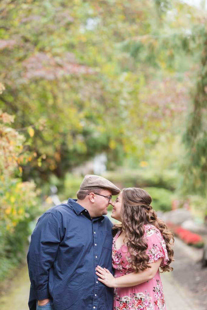 The couple, standing amongst the trees, smiling at one another, nose to nose, dressed up for their Sayen Gardens engagement photos