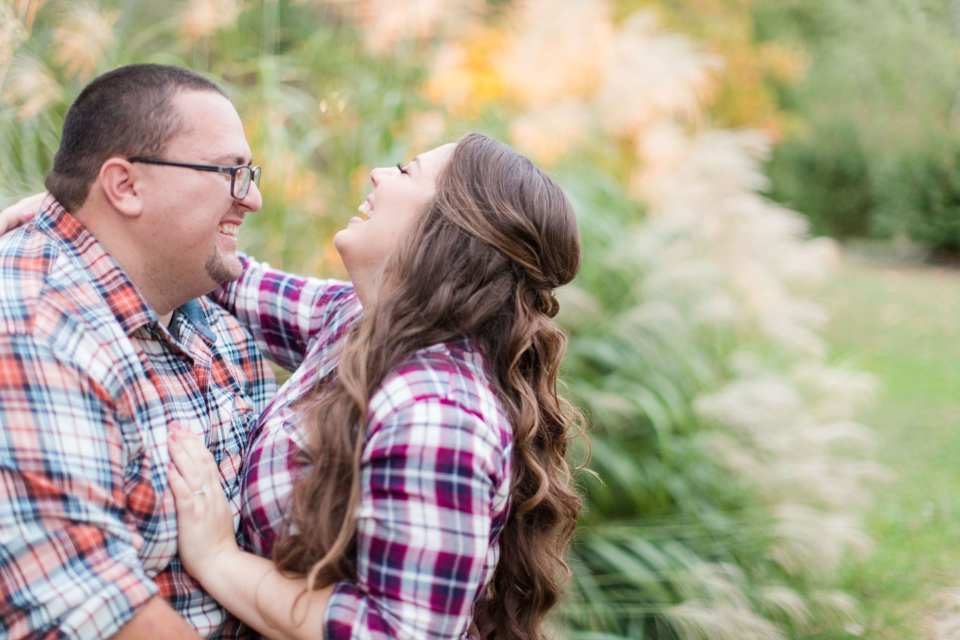 Engaged couple laughing while in one anothers arms during their Sayen Gardens engagement photos