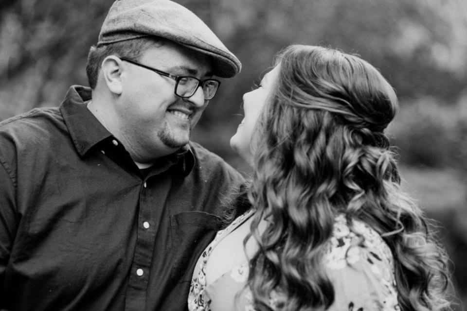 Black and white photo of the engaged couple smiling at one another, his face in view