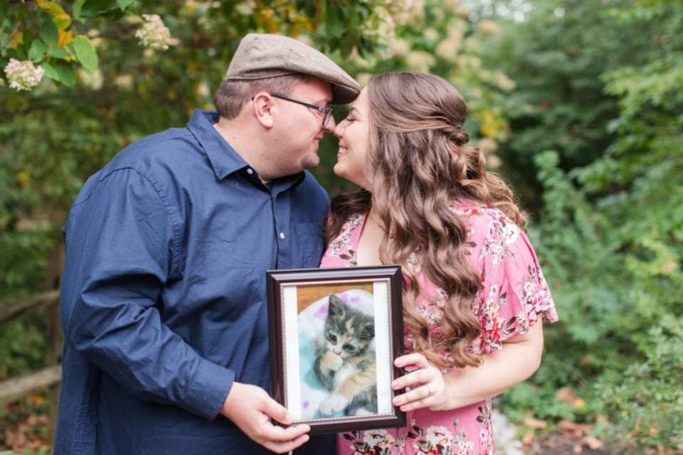The engaged couple, nose to nose, smiling, holding a framed photograph of their kitten