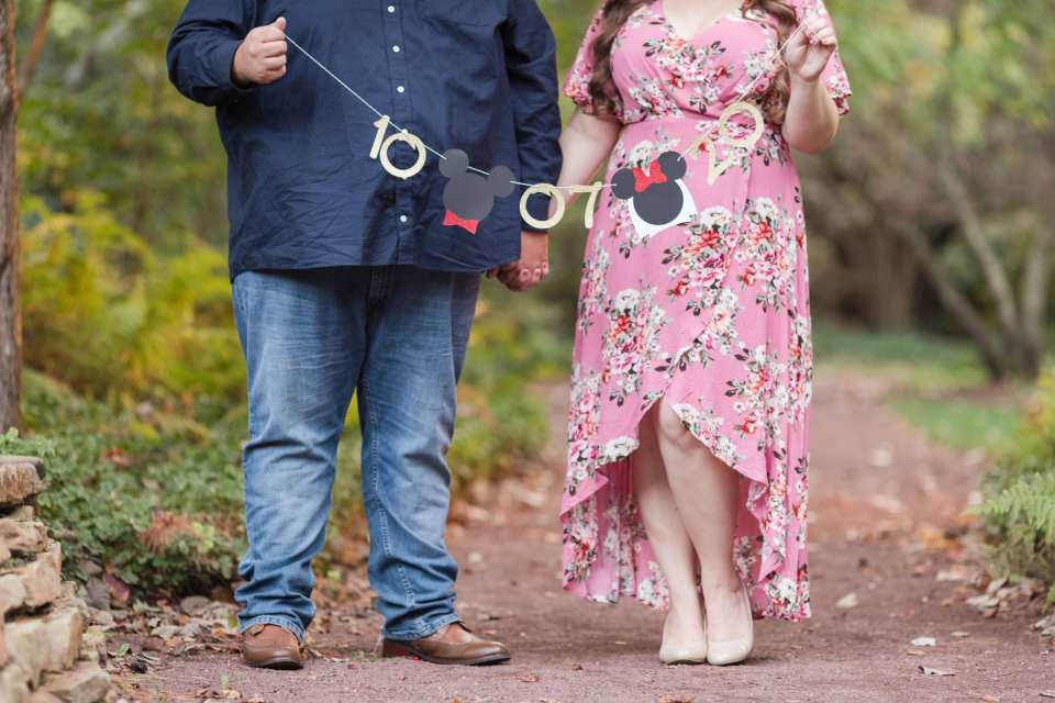 3/4 shot of the engaged couple, dressed up, each holding one end of a custom wedding date banner with Mickey and Minnie Mouse silhouette's by House of Paper by Alana